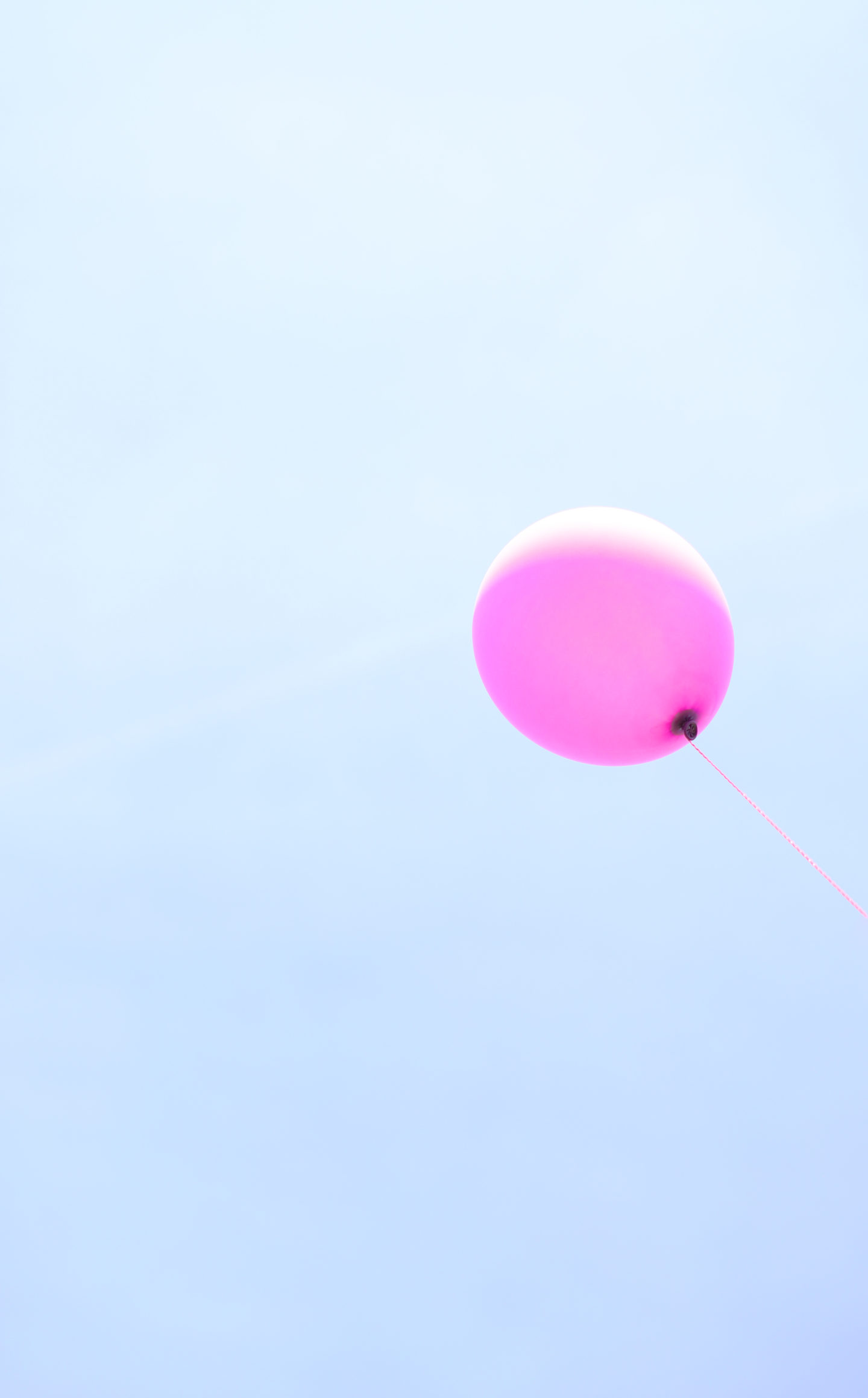a purple ballon in a blue sky