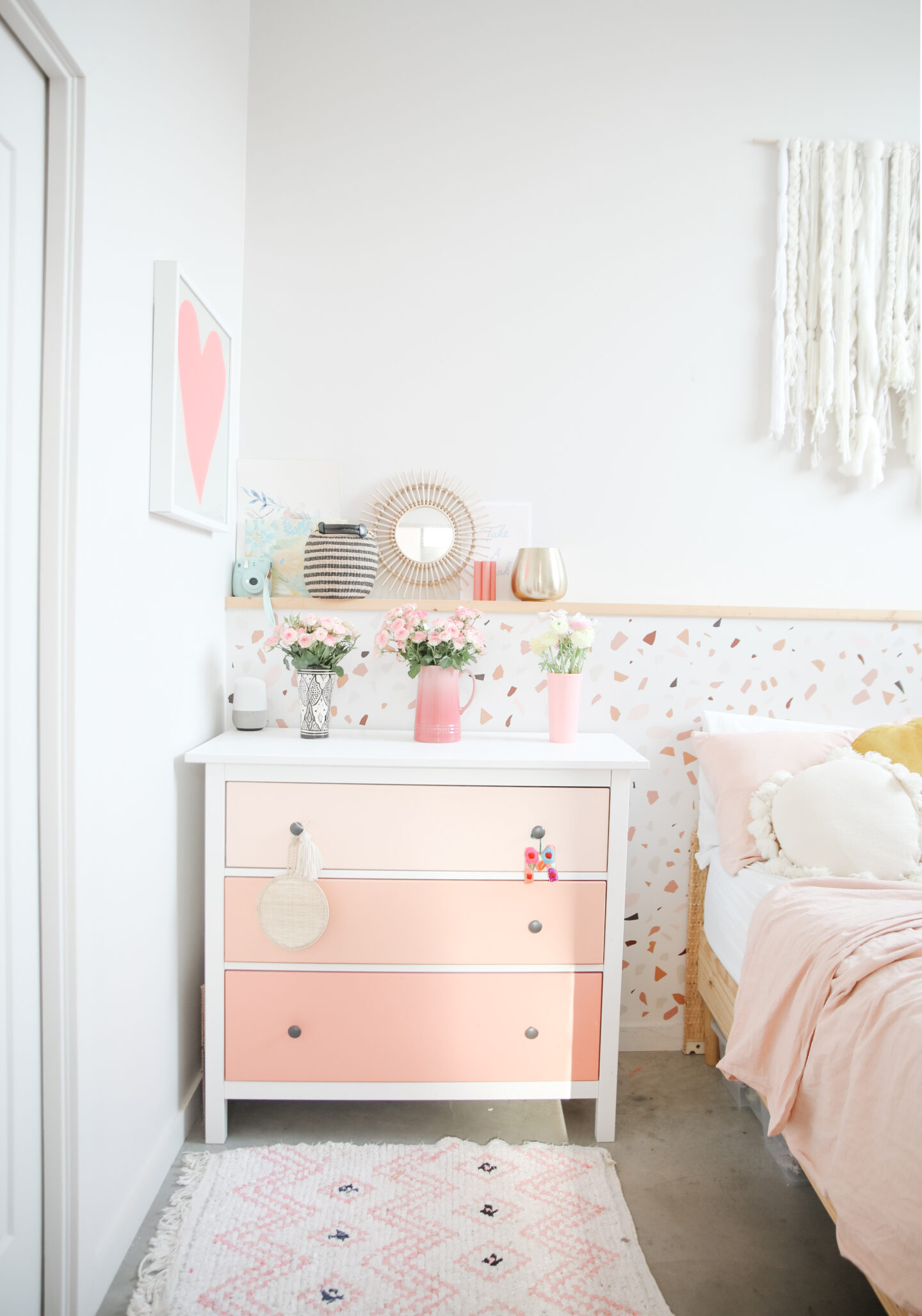 bright pink dresser with a terrazzo wall behind